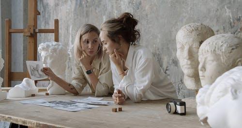 Two Women Looking At Drawings Inside An Art Workshop