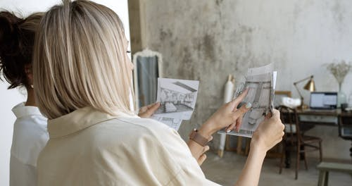 Two Women Looking At Drawings And Comparing Them