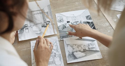 Women Looking At Interior Designs Laid Over The Table