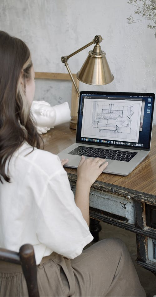 A Woman Using A Computer Laptop In Making A Design