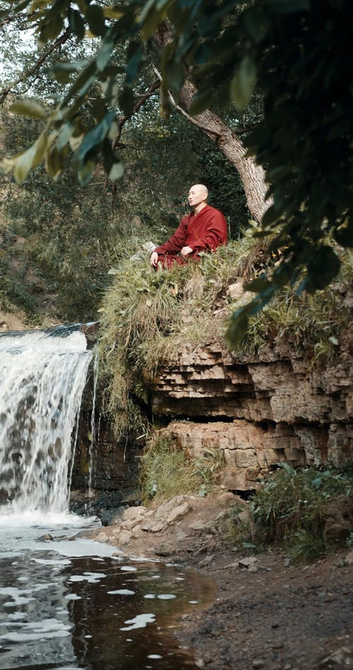 A Monk Meditates By The Riverside In Lotus Position