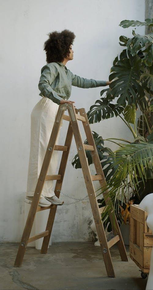 Woman Standing on Stairs and Touching  Palm Leaves
