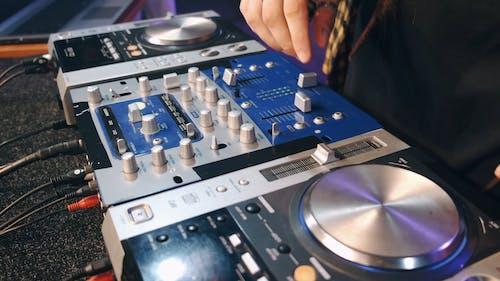 A DJ Working On A Sound Mixer