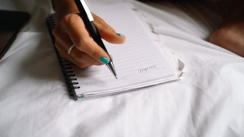 Female Hand Writing in Notebook Close up