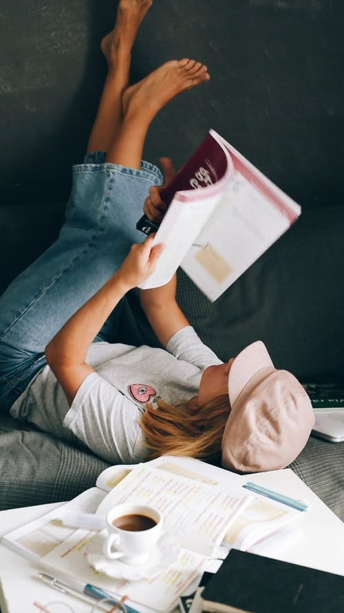 Young Woman Reading a Book Lying Down