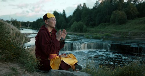 Tibetan Monk with Ringing Hand Bell next to Cascade