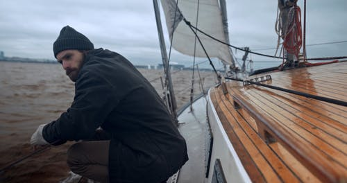 A Man Crouching on the Side of the Boat
