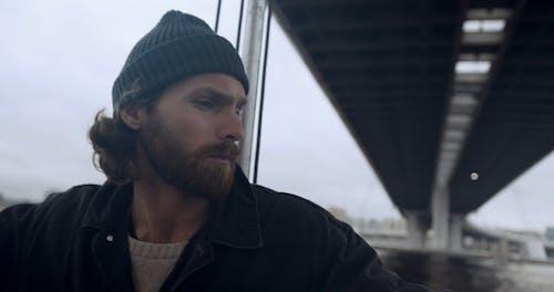 A Man on a Sailing Boat Crossing a Bridge