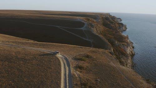 Aerial View of Car Driving Along Coastal Road
