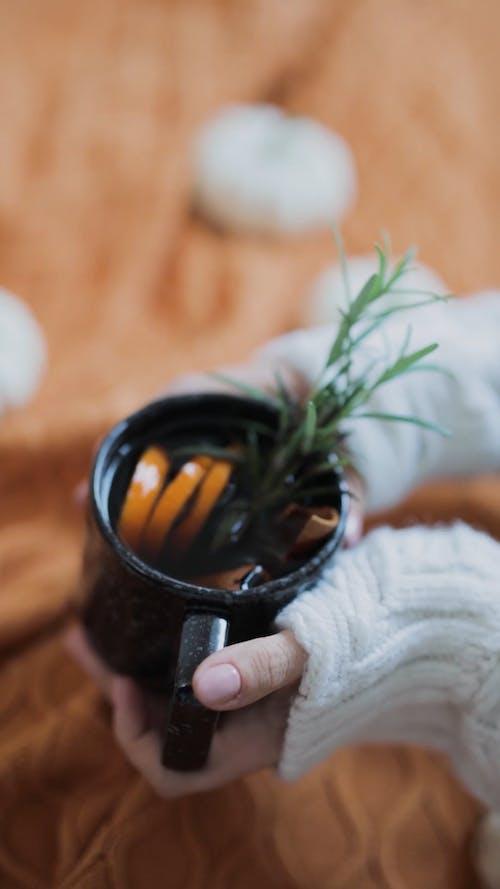 Female Hands Stirring Herbal Tea