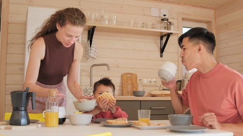 Little Boy Eating Breakfast with Parents