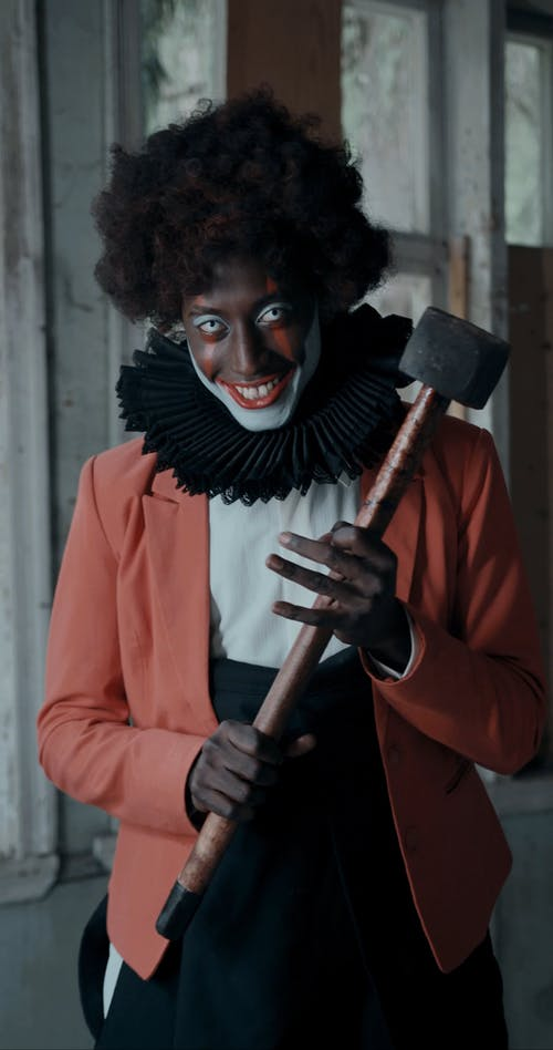 Creepy Smiling Clown with Hammer Looking at Camera