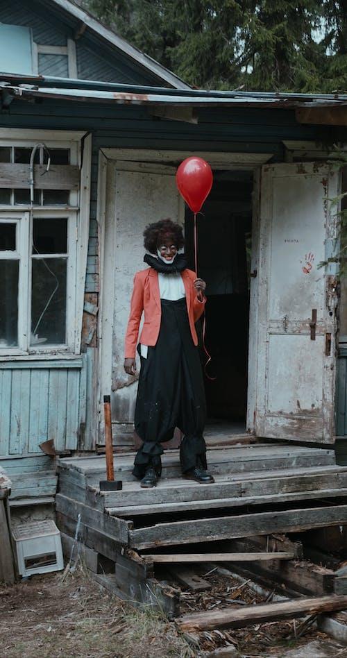 Creepy Clown with Red Balloon Waving Hand