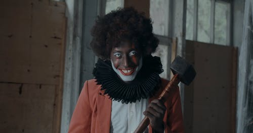Creepy Clown Smiling and Swinging Hammer