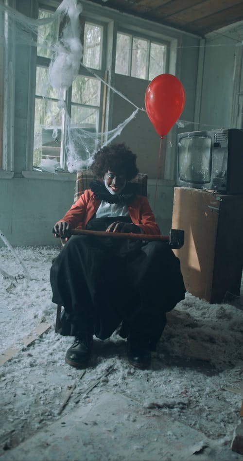 Creepy Smiling Clown Sitting with Hammer