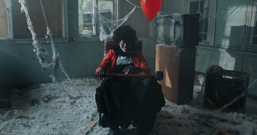 Creepy Smiling Clown Sitting with Hammer and Red Balloon