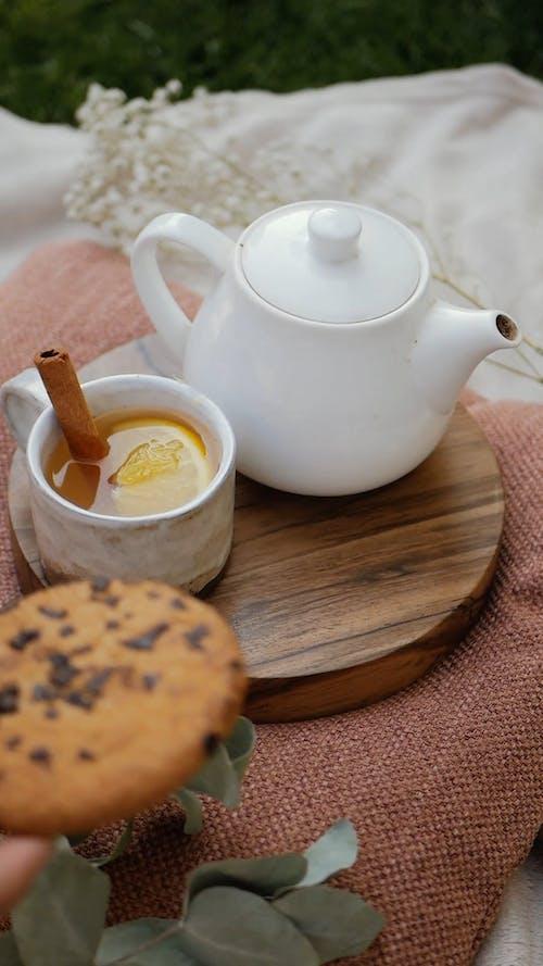 Placing chocolate chip cookie with Lemon Honey Tea