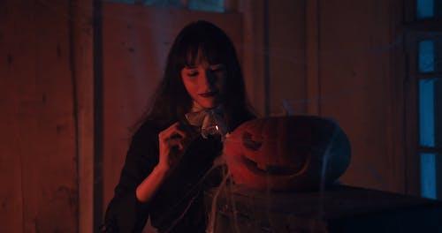 Woman Lighting a Pumpkin Lamp