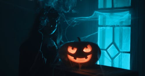 Young Woman with Glowing Halloween Pumpkin
