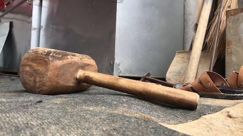 Man Picking up a Wooden Hammer