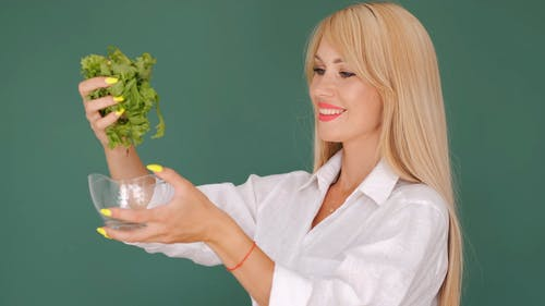 Woman Putting Chopped Lettuce in a Bowl