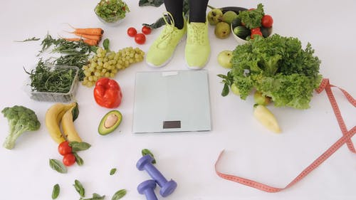 Woman Standing in Weighing Scale Surrounded by Vegetables and Fruits