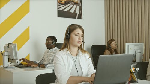 Female Customer Service Staff Working on Laptop and Talking Customer