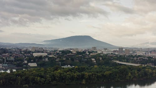 Aerial View City with Green Mountain Background