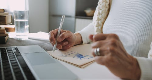 An Elderly Woman Drawing Sketches And Writing Notes