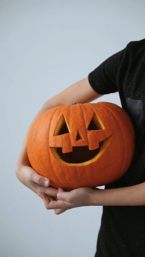 A Person Holding a Carved Pumpkin