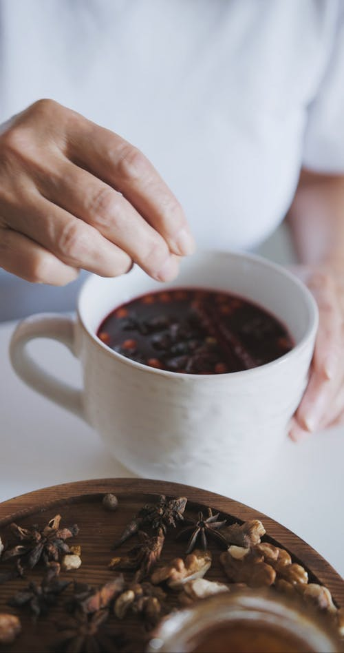 A Person Adding Spices on a Cup of Tea