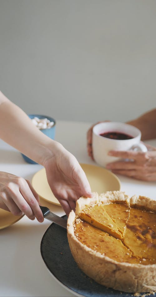 A Person Getting Slice of Pumpkin Pie into the Plate