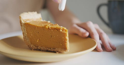 Close-Up View of a Pumpkin Pie With Whipped Cream on Plate