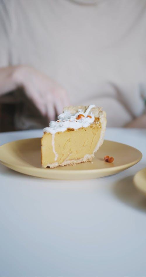 A Woman in Beige Shirt Holding a Pumpkin Pie on a Plate