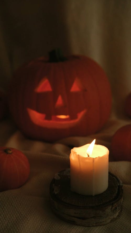 A Lighted Candle Blown Out Near a Carved Pumpkin