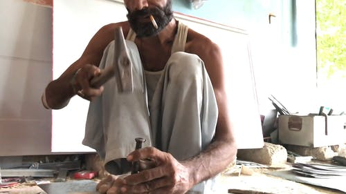 A Bearded Man Hammering a Big Nail