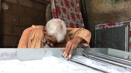 An Elderly Man Hammering Nail on Iron Sheets