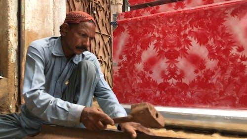 A Man Hammering a Iron Sheets