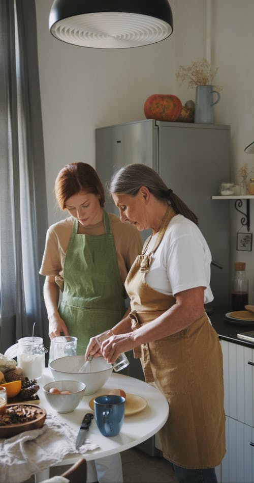 An Elderly Woman Teaching Her Daughter To Bake