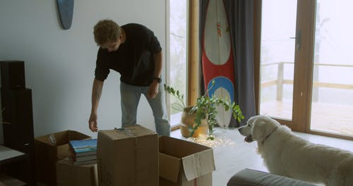 A Man Picking Up a Box the Giving it to the Woman