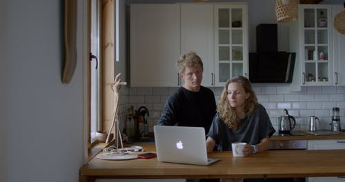 A Couple Looking at the Laptop While Talking to Each Other