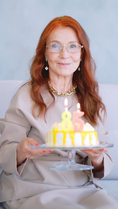 A Woman Blowing Off Her Birthday Cake