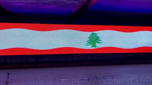 Vehicle Passing by a Lebanon Flag on Digital Screen