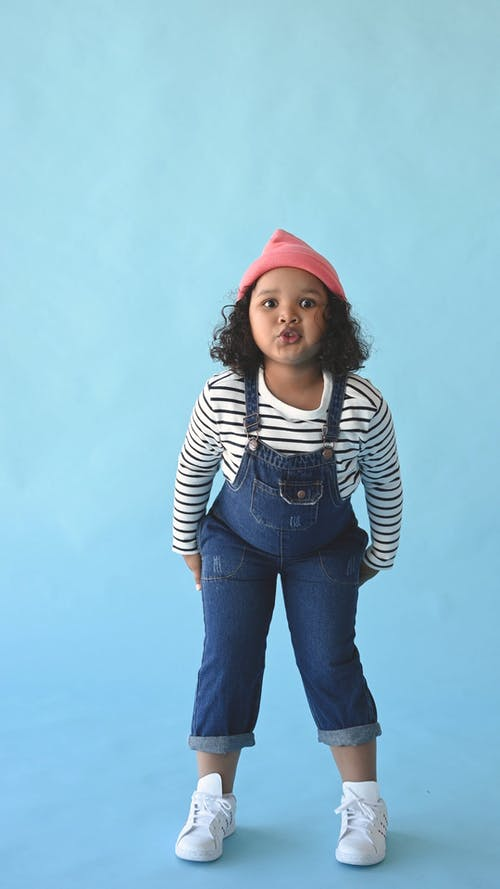 Girl Wearing an Overalls Against a Blue Background