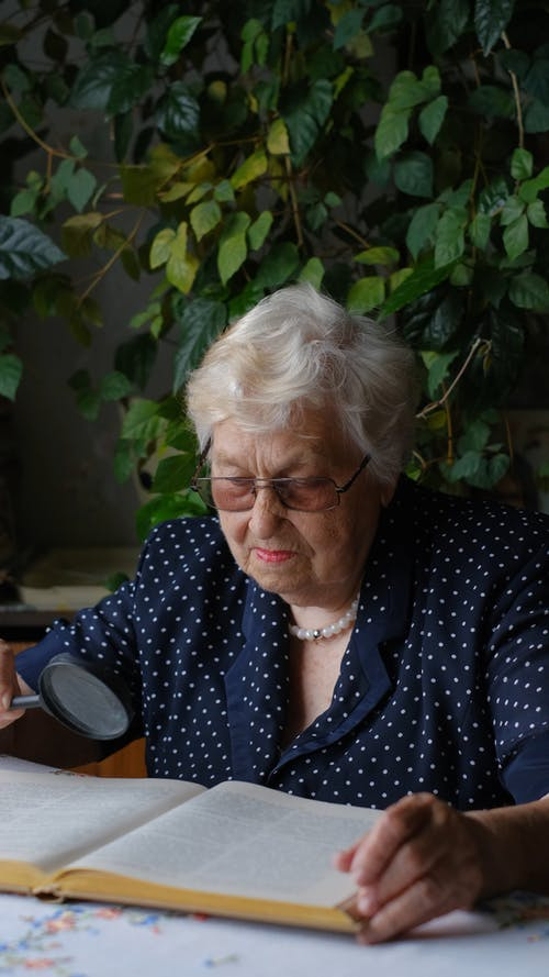 An Elderly Woman Reading Using a Magnifying Glass