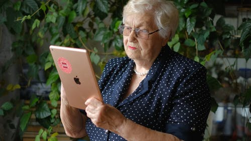 An Elderly Woman Using An Electronic Tablet