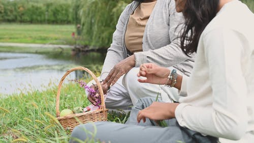 Women Decorating Their Basket With Grass Flowers