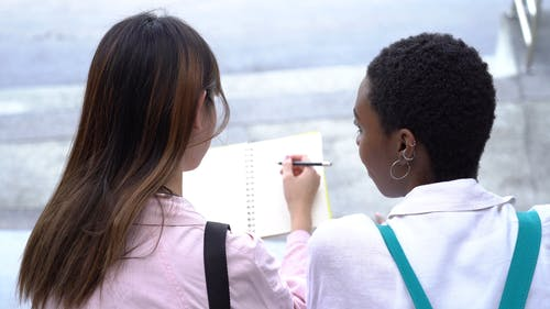 Two Ladies Reviewing School Works Outdoors