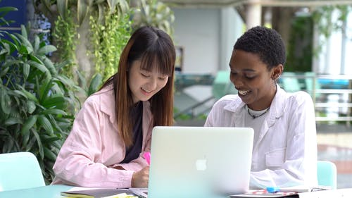 Two Young Woman Having Fun While Studying