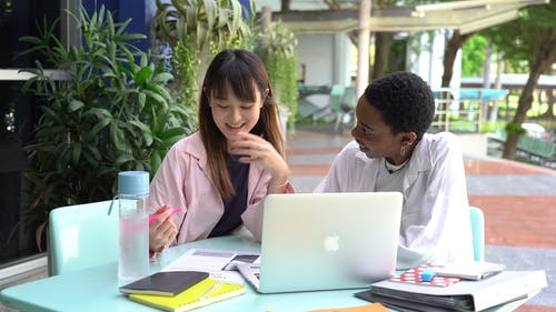 An Asian Student Being Tutored By A Fellow Student